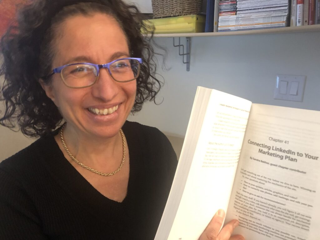 Sandra Bekhor holds LinkedIn® Marketing Techniques book open to the chapter she wrote: Connecting LinkedIn to Your Marketing Plan